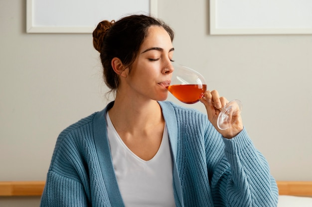 Vista lateral de mulher bebendo em casa