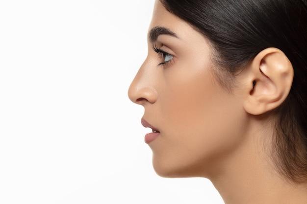 Vista lateral de mulher bonita isolada na parede branca