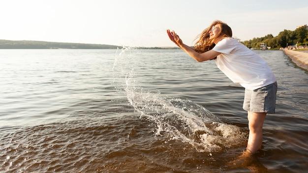 Vista lateral de mulher brincando com água à beira do lago