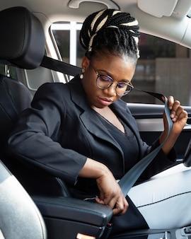 Vista lateral de mulher colocando o cinto de segurança para dirigir