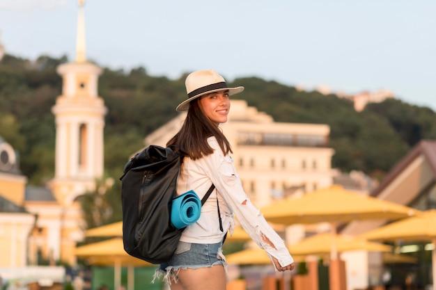 Vista lateral de mulher com chapéu carregando mochila enquanto viaja