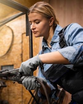 Vista lateral de mulher com ferramenta de soldagem