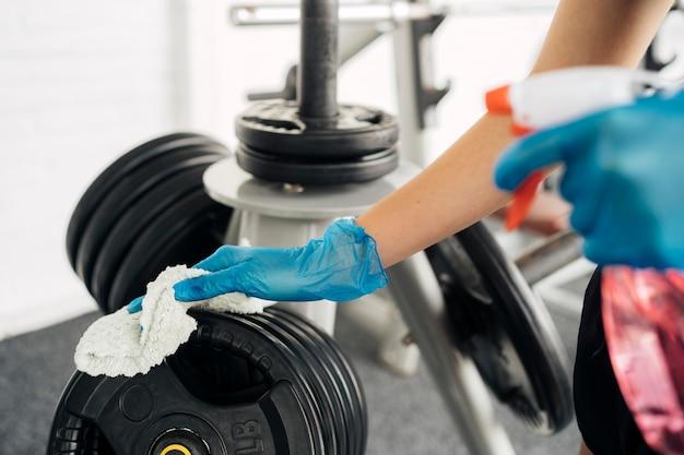Vista lateral de mulher com luvas no ginásio desinfetando equipamentos