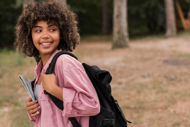 Vista lateral de mulher com mapa e mochila ao ar livre