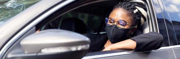 Vista lateral de mulher com máscara, dirigindo o carro