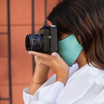 Vista lateral de mulher com máscara facial usando câmera