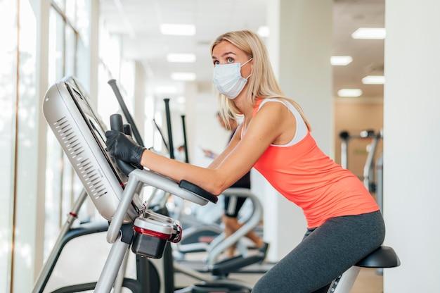 Vista lateral de mulher com máscara médica e luvas, malhando na academia