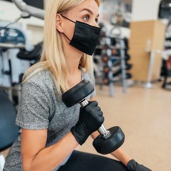 Vista lateral de mulher com máscara médica e luvas treinando na academia