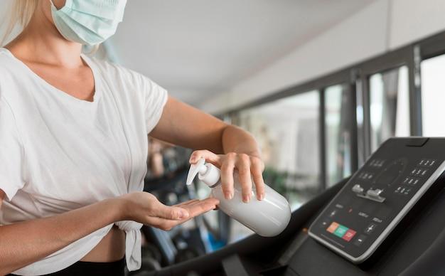 Vista lateral de mulher com máscara médica usando desinfetante para as mãos na academia enquanto está na esteira