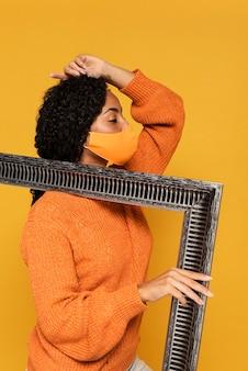 Vista lateral de mulher com máscara posando com moldura