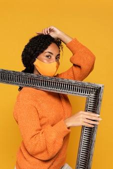 Vista lateral de mulher com máscara segurando moldura