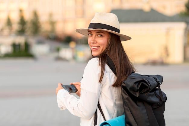 Vista lateral de mulher com mochila e chapéu enquanto viaja sozinha