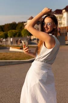 Vista lateral de mulher com óculos escuros e smartphone posando ao ar livre