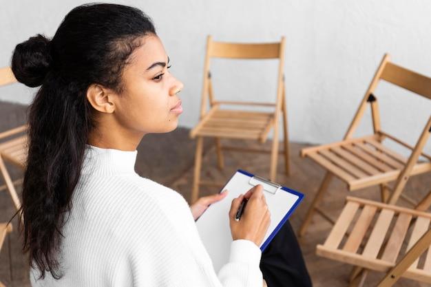 Vista lateral de mulher com prancheta em uma sessão de terapia de grupo
