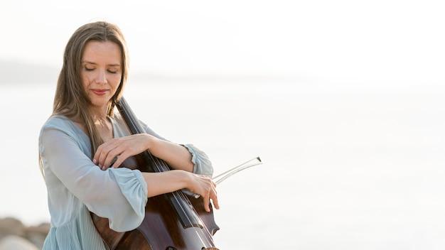 Vista lateral de mulher com violoncelo e espaço de cópia