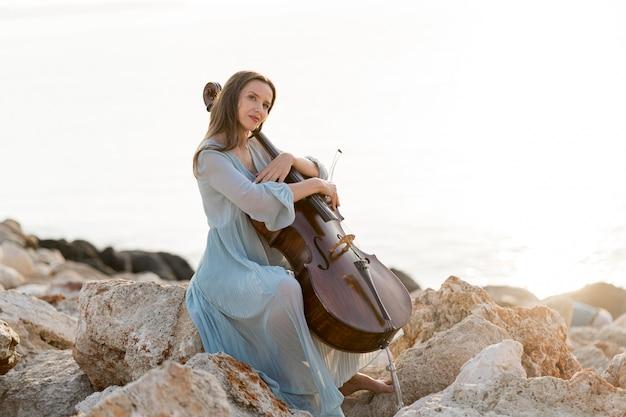 Vista lateral de mulher com violoncelo sobre pedras