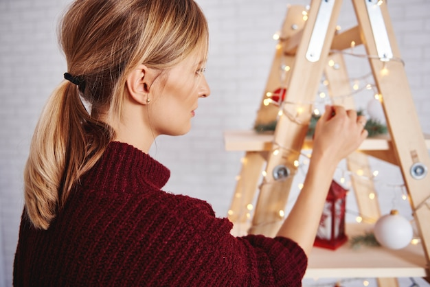Vista lateral de mulher decorando a árvore de natal