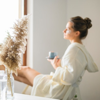 Vista lateral de mulher desfocada, desfrutando de um dia de spa em casa enquanto tomando café