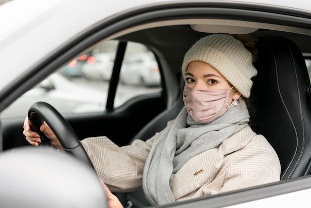 Vista lateral de mulher dirigindo com máscara médica