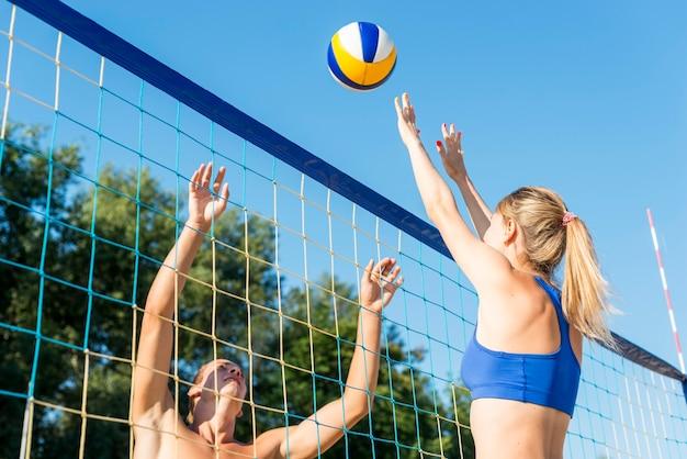 Vista lateral de mulher e homem jogando vôlei de praia