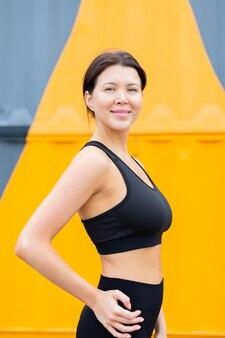 Vista lateral de mulher em athleisure posando ao ar livre