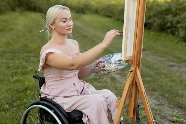 Vista lateral de mulher em cadeira de rodas pintando ao ar livre