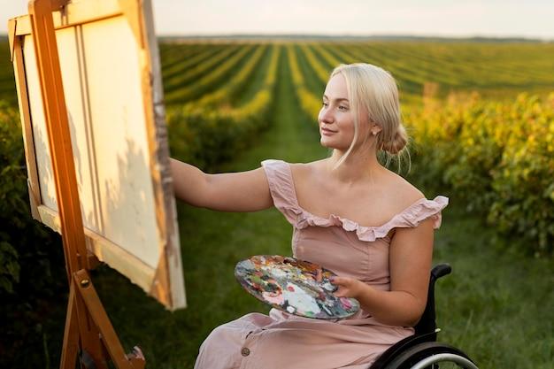 Vista lateral de mulher em cadeira de rodas pintando do lado de fora