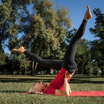 Vista lateral de mulher em posição de ioga ao ar livre