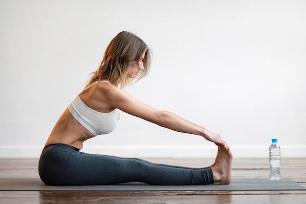 Vista lateral de mulher em tapete de ioga com garrafa de água