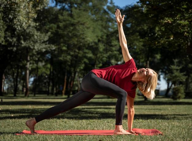 Vista lateral de mulher exercitando posição de ioga ao ar livre