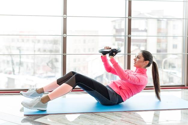 Vista lateral, de, mulher, exercitar, com, peso, prato