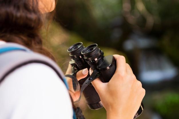 Vista lateral de mulher explorando a natureza com binóculos