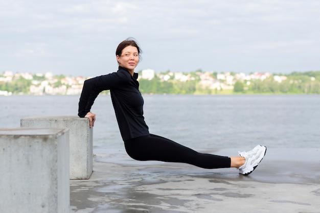 Vista lateral de mulher fazendo exercícios ao ar livre