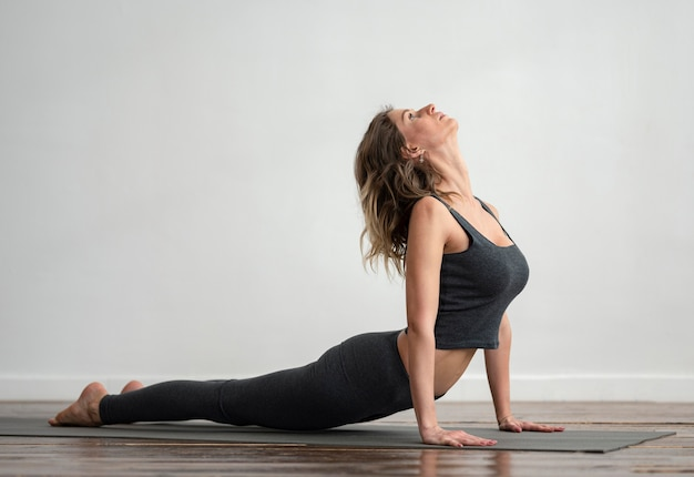 Vista lateral de mulher fazendo ioga em casa com espaço de cópia