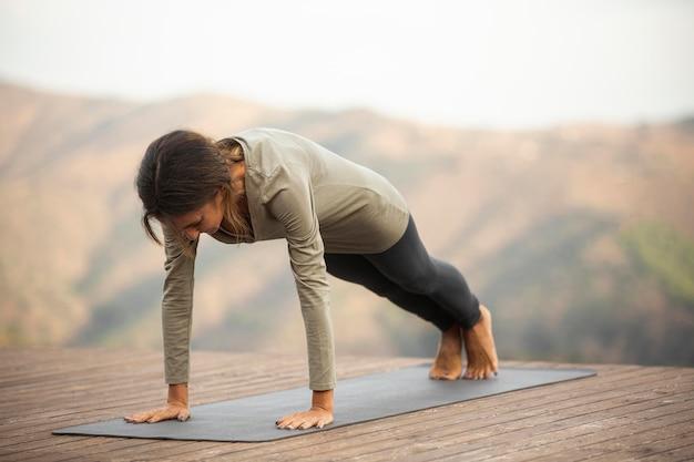 Vista lateral de mulher fazendo ioga na natureza