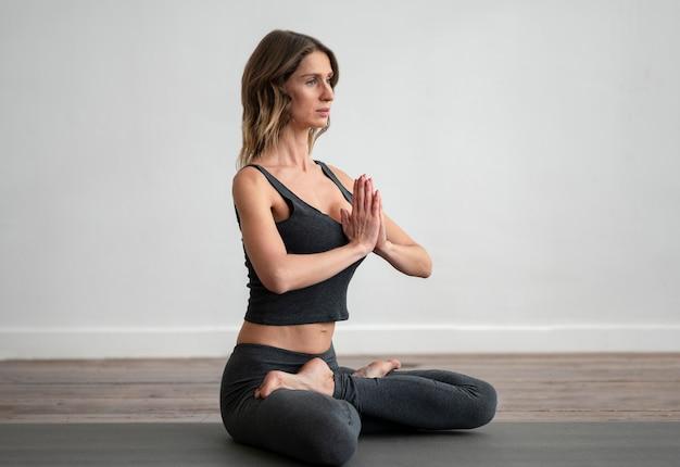 Vista lateral de mulher fazendo ioga no tapete