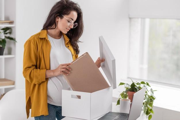 Vista lateral de mulher grávida arrumando a caixa em casa
