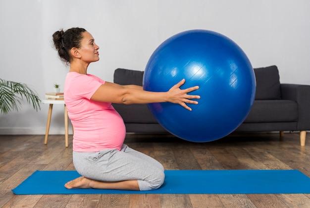 Vista lateral de mulher grávida se exercitando no colchonete em casa com a bola