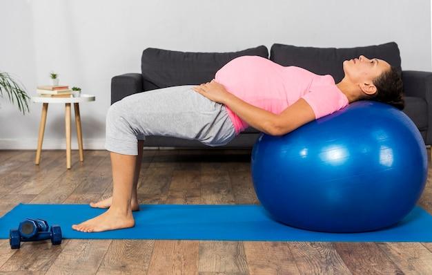 Vista lateral de mulher grávida usando bola para se exercitar em casa