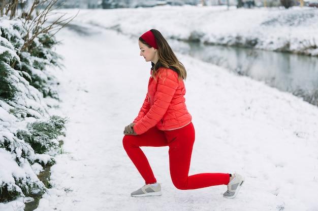 Vista lateral, de, mulher jovem, esticar, dela, perna, em, inverno