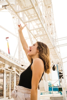 Vista lateral, de, mulher jovem, fazendo divertimento, em, parque divertimento