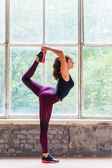 Vista lateral, de, mulher jovem, fazendo, ioga posa, perto, a, janela vidro