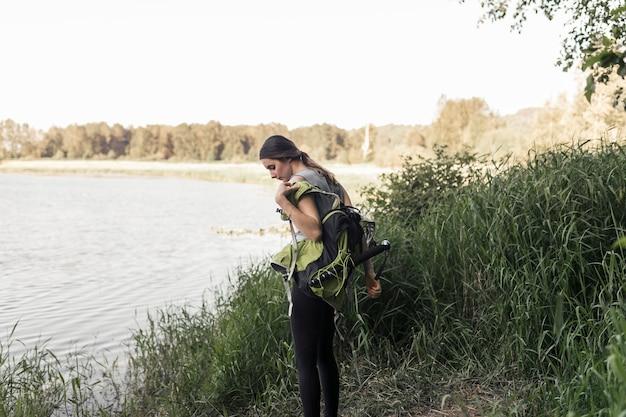 Vista lateral, de, mulher jovem, ficar, perto, a, lago, pôr, dela, mochila