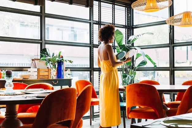 Vista lateral, de, mulher jovem, olhar, dois, diferente, pratos, em, a, restaurante