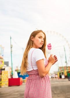 Vista lateral, de, mulher jovem, segurando, grande, pirulito, em, parque divertimento