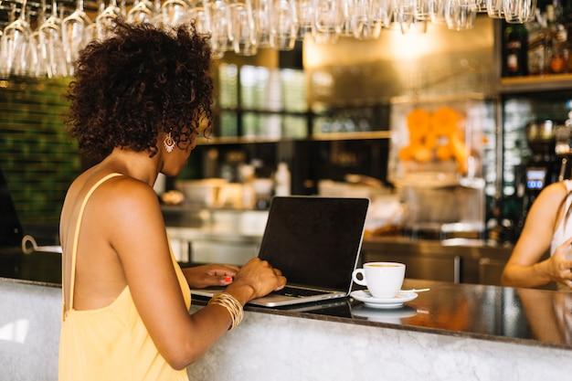 Vista lateral, de, mulher jovem, usando computador portátil, em, barra, contador
