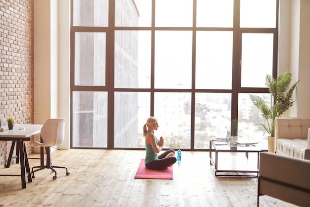 Vista lateral de mulher madura esportiva sentada em um tapete e assistindo a um vídeo tutorial online usando um laptop