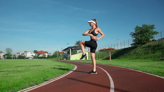 Vista lateral de mulher magra praticando exercícios de joelhos altos antes de correr no estádio. atordoamento apto garota vestindo roupas esportivas pretas e boné branco treinando em um dia ensolarado de verão, aquecendo. conceito de esporte.