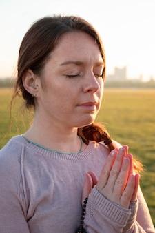 Vista lateral de mulher meditando ao ar livre