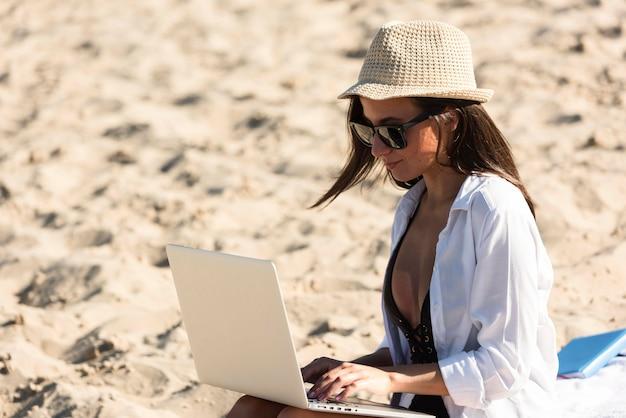 Vista lateral de mulher na praia com laptop